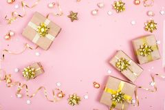 Fashion gifts or presents boxes with golden bows and star confetti on pink pastel background top view. Flat lay composition for stock image