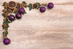 Christmas frame. With purple decoration, dry orange and leaves on black wood background with copy space Stock Photo