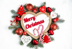 Christmas frame in the shape of a heart surrounded by branches of a New Year tree, red Christmas decorations with copy stock photography