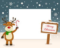 Christmas Frame Sign & Happy Reindeer. Christmas horizontal photo frame with a happy reindeer smiling and holding a candy cane in a snowy scene with a merry Royalty Free Stock Image