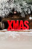 Christmas Frame from Snowy Fur tree branches, Wooden Xmas Letter. S and Glass Balls on rustic background royalty free stock photos