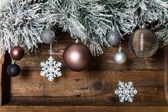Christmas Frame from Snowy Xmas tree branches. And Glass Balls on wooden background royalty free stock image