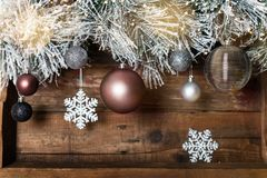 Christmas Frame from Snowy Xmas tree branches. And Glass Balls on wooden background stock images