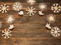 Christmas frame with straw snowflakes and angels on a dark woode. N background. Holidays Concept Stock Photos