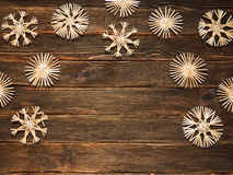 Christmas frame with straw snowflakes on a dark wooden backgroun. D. Holidays Concept Royalty Free Stock Photos