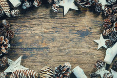 Christmas frame. Vintage Christmas frame with pinecones and stars on wooden background Royalty Free Stock Image