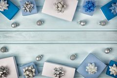 Christmas frame. White and blue gift boxes decorated with silver bows. Small Christmas balls. Copy Space. Holiday layout. With place for text on a light blue stock image
