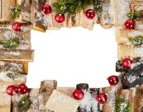 Christmas frame with winter snow, logs and baubles. Christmas frame with winter snow, logs and colorful red baubles with fronds of pine isolated on white with royalty free stock images