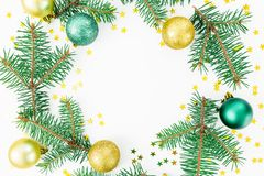 Christmas frame of winter trees, golden balls and confetti on white background. Winter concept. Flat lay, top view. Christmas frame of winter trees, golden balls Stock Photo