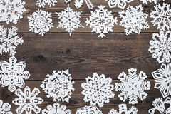 Christmas frame - wooden background with snowflakes. Christmas decoration with paper snowflake  - copy space Stock Images