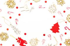 Christmas frame with wooden tree decoration, snowflakes and candy canes on white background. Flat lay, top view. New Year concept. Christmas frame with wooden royalty free stock photography