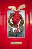 Christmas front door with handmade reindeer wreath. Bright red christmas front door with handmade reindeer wreath Stock Photo