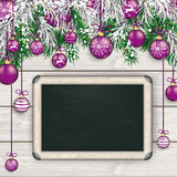 Christmas  Frozen Green Fir Twigs Wood Blackboard. Christmas card with with snow, purple baubles and fir twigs Stock Photos