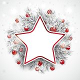 Christmas Frozen Twigs Snowfall Baubles Star. Red paper star with frozen twigs, red baubles and snowfall in the back Royalty Free Stock Photos