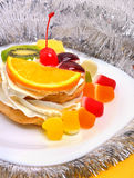 Christmas fruit cake with cream on white plate and silver tinsel Royalty Free Stock Photos