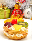 Christmas fruit cake with cream on white plate and silver tinsel Royalty Free Stock Image