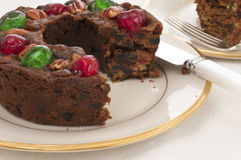 Christmas Fruit Cake with red and green cherries on top on a China Plate on a Table with a White Table Cloth. Horizontal of table setting with a fruit cake with Royalty Free Stock Photo