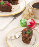 Christmas Fruit Cake with red and green cherries on top on a China Plate on a Table with a White Table Cloth Stock Photo