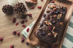 A christmas fruit cake on a wooden plate. A fresh home-made chocolate christmas fruit cake served on a wooden plate with some raisins and and kitchen cloth on Royalty Free Stock Images