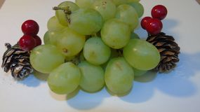 Christmas fruit. Close up of a bunch of grapes with two cones and berries Royalty Free Stock Photography