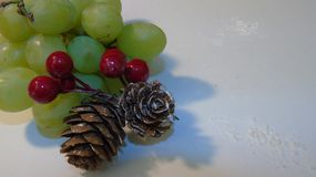 Christmas fruit. Close up of a bunch of grapes with two cones and berries Stock Photo