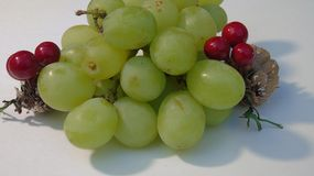 Christmas fruit. Close up of a bunch of grapes with two cones and berries Stock Photos