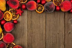 Christmas fruit decoration corner border over rustic wood. Christmas fruit decoration corner border over a dark rustic wood background royalty free stock images