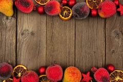 Christmas fruit decoration double border over rustic wood. Christmas fruit decoration double border over a dark rustic wood background stock photography