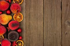 Christmas fruit decoration side border over rustic wood. Christmas fruit decoration side border over a dark rustic wood background stock photography