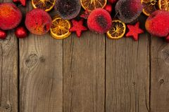 Christmas fruit decoration top border over rustic wood. Christmas fruit decoration top border over a dark rustic wood background stock photos