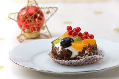 Christmas fruit fancy cake. Christmas decorated table with a piece of a fancy fruit cake Stock Image
