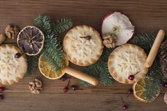 Christmas Fruit mince tarts. Fir branches and christmas decorations. Rustic wooden background royalty free stock photos