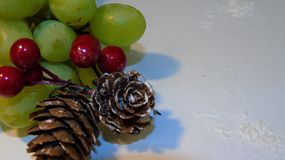 Christmas fruit. Small bunch of grapes with two cones and berries Stock Photos