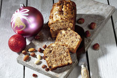 Christmas fruitcake with nuts and christmas decorations on wooden board Stock Image