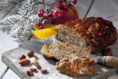 Christmas fruitcake with nuts and fruits and christmas decorations on wooden board Stock Photography