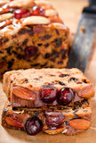 Christmas fruitcake slices on chopping board. Stock Photo