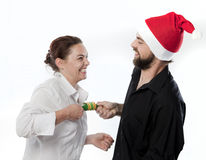 Christmas Fun. Man in santa hat and woman pulling a party cracker Royalty Free Stock Photography