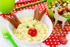 Christmas fun food art idea for kids breakfast or festive dinner. Cute reindeer from couscous porridge with sausage and vegetables Stock Images