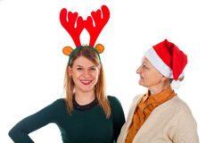 Christmas fun. Picture of two happy ladies wearing Christmas costumes on an isolated background Royalty Free Stock Image