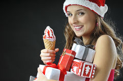 Christmas funny  girl with ice cream. Covered  gifts wearing Santa hat Royalty Free Stock Photos