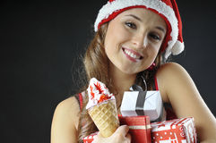 Christmas funny  girl with ice cream. Covered  gifts wearing Santa hat Stock Photos