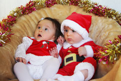 Christmas funny small kids in Santa Claus clothes. Twins, a boy and a girl Royalty Free Stock Photos
