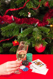 Christmas gambling. Woman hand holding a wine glass near casino chips and cards on red table Stock Images