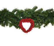 Christmas garland. Pine garland decorated with red heart Royalty Free Stock Images
