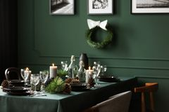 Christmas garland and black and white posters on green wall of dining room set for christmas dinner. Christmas garland and black and white posters on green wall royalty free stock images
