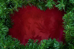 Christmas Garland Border. Over rich red brocade fabric. Lots of copy-space royalty free stock images