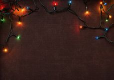 Christmas garland with colorful lights on brown textile stock photos