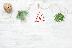 Christmas garland of conifer branches & red christmas tree against white wooden background. royalty free stock image