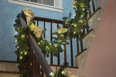Christmas garland draped over bannister. Christmas garland with white lights and yellow bows draped over bannister royalty free stock photos