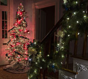 Christmas garland draped over bannister. Christmas garland with white lights and yellow bows draped over bannister with Christmas tree at the base of the stairs stock image